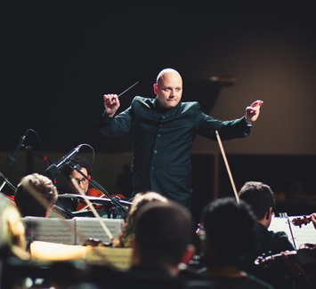 Man performing on stage (conductor, facilitator)
